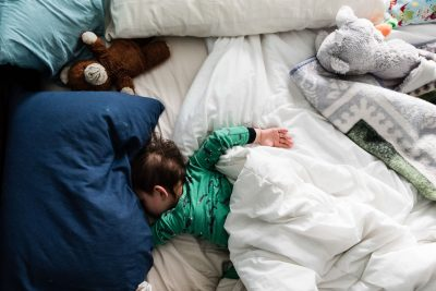 boy sleeping in messy bed with stuffed animals