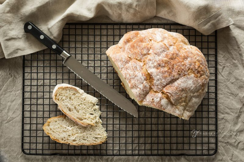 artisan goodness homemade bread with knife on cooling rack