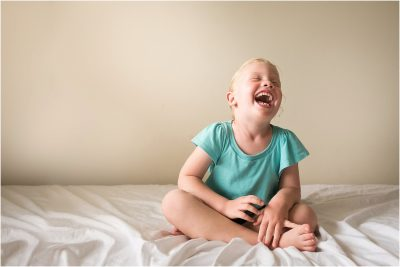 little girl giggling on her bed