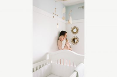 A mother holds her sleeping infant son in the nursery, looking into the distance.