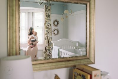 Mother and baby in nursery seen reflected in mirror.