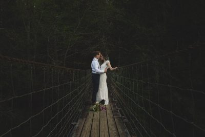 Couple nuzzling on a swinging bridge in the forest for elopement photos by Tami Keehn