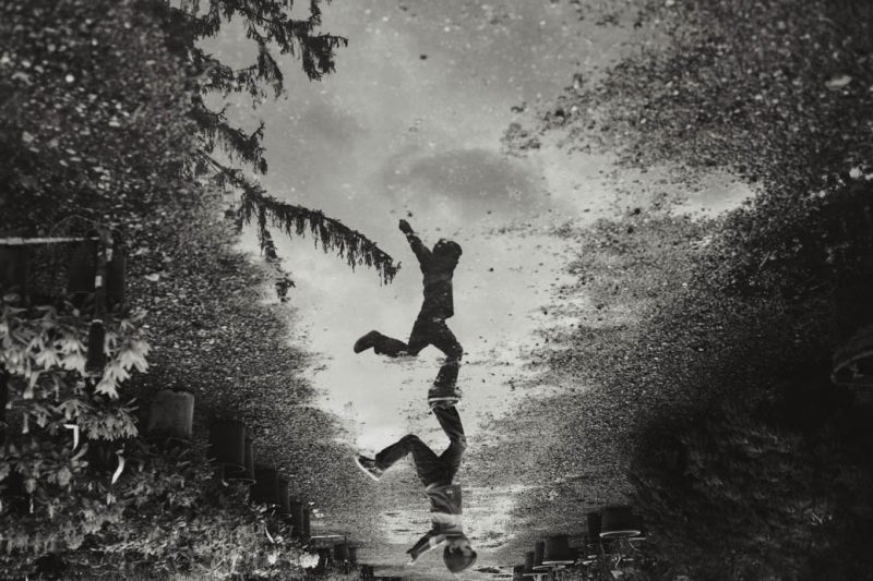 boy_leaps_over_puddle_reflection