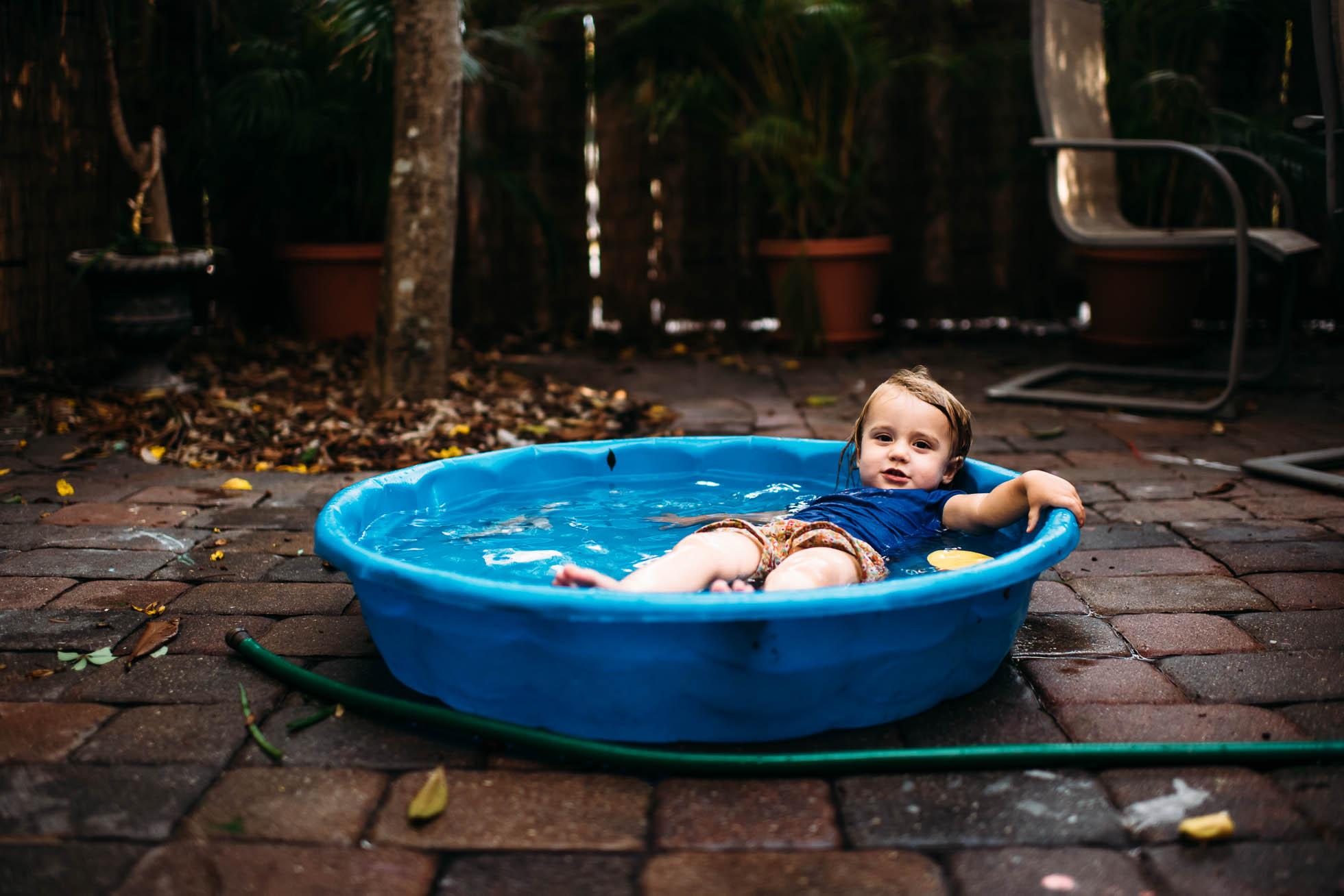 Toddler wearing clothes in kiddie pool.