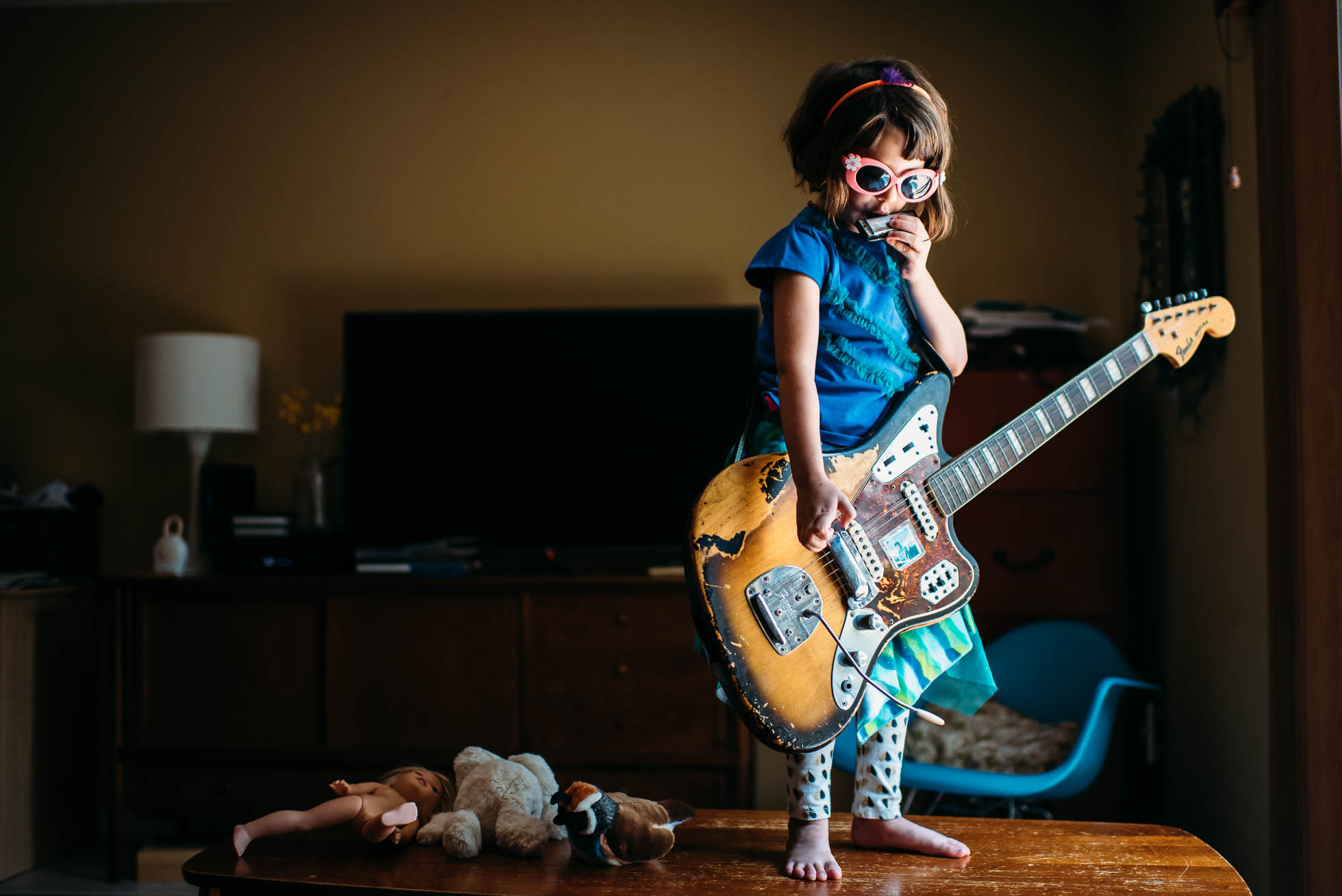 Girl in sunglasses playing guitar.