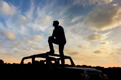 teenage boy silhoutte sitting on top of jeep