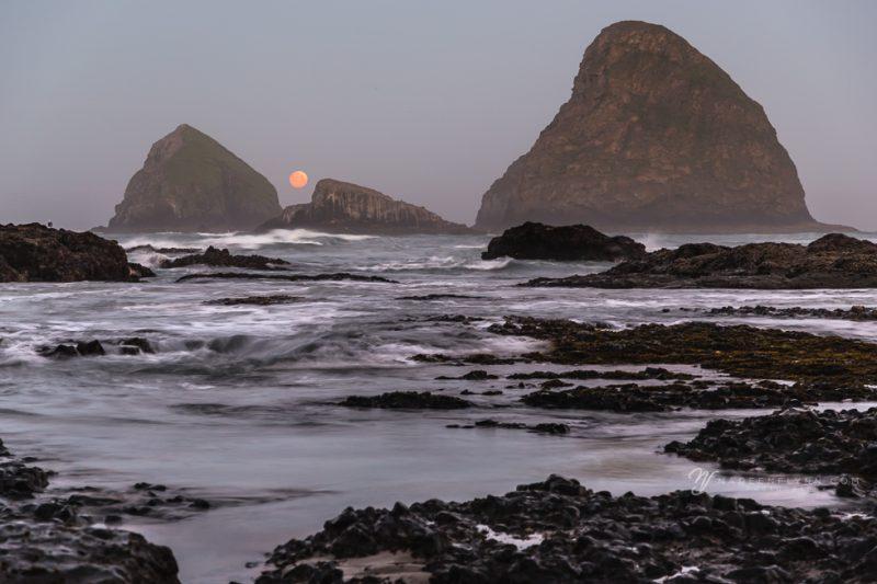 moon setting between two rocks on the Oceanside Beach in Oregon