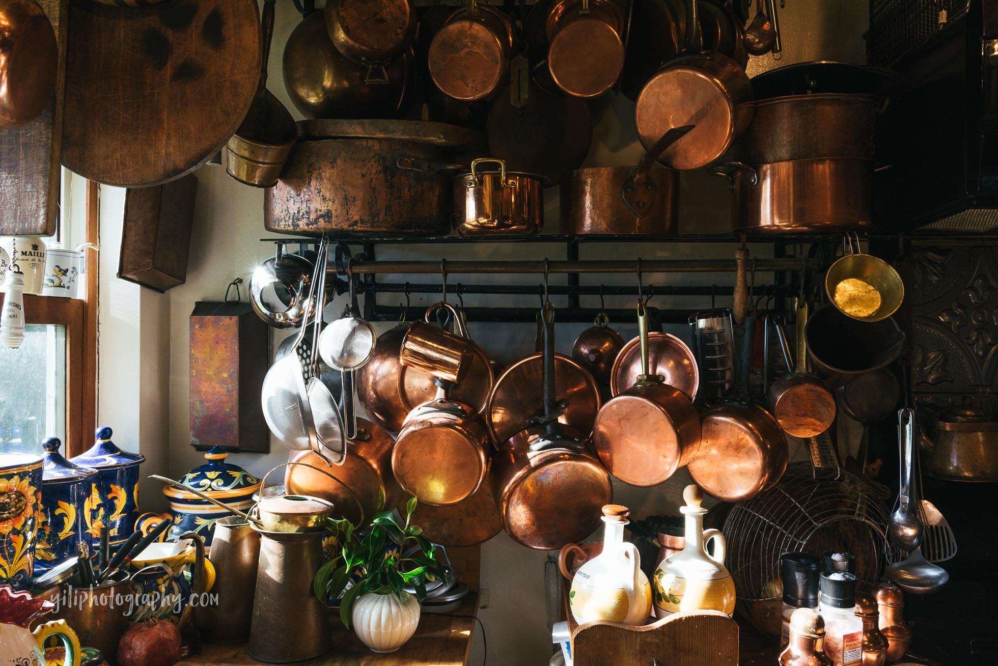 large collection of copper pots and pans hanging in kitchen