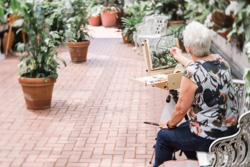 Woman paints on canvas at Biltmore Conservatory