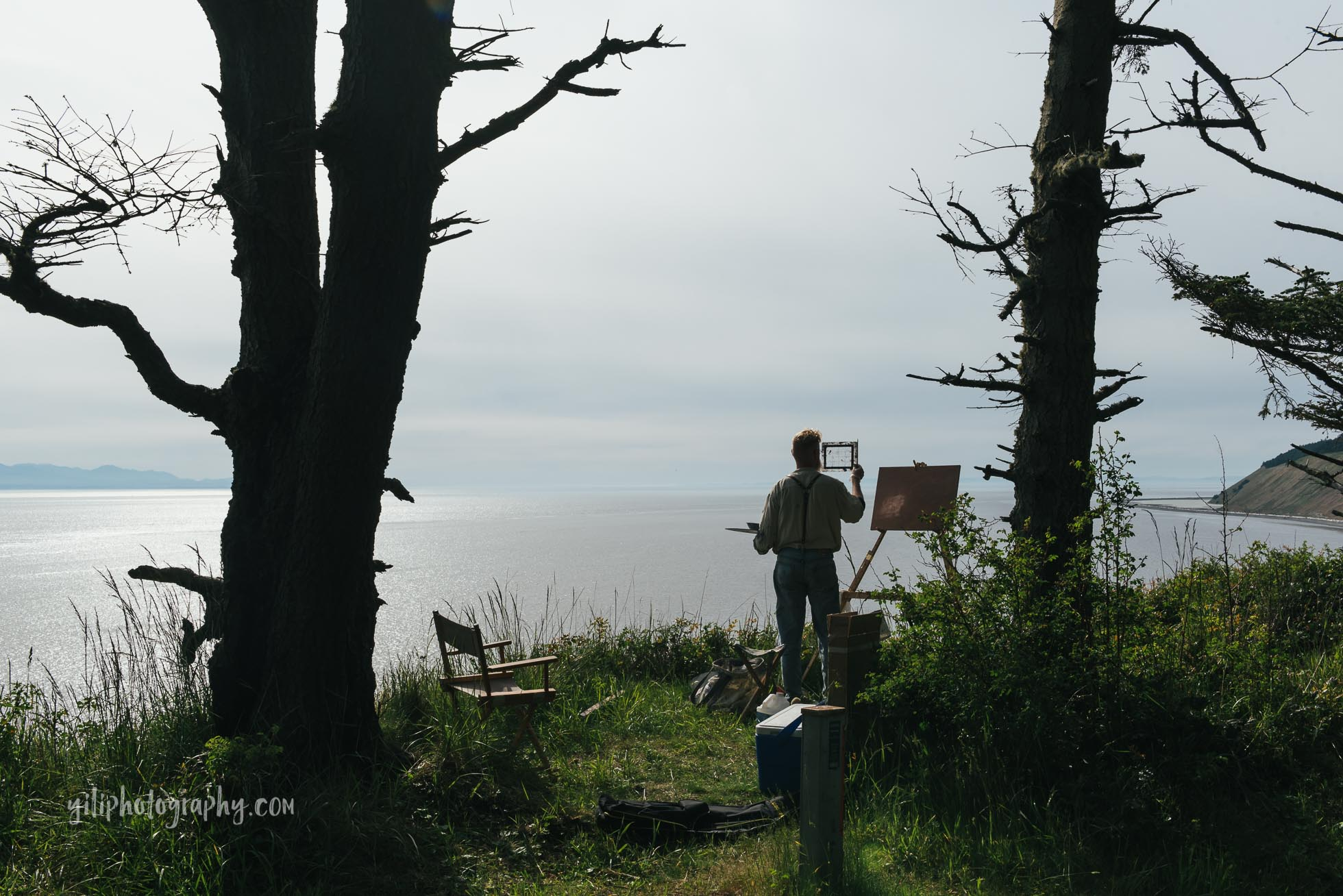 Plein air painter holding grid in front of canvas on easel