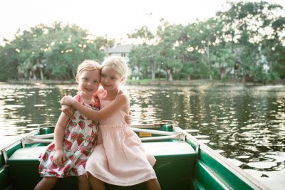 two little girls in a green boat at solden hour tiffany kelly