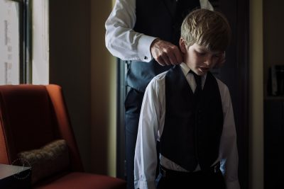 A boy (ring bearer) gets help with his tuxedo from his dad.