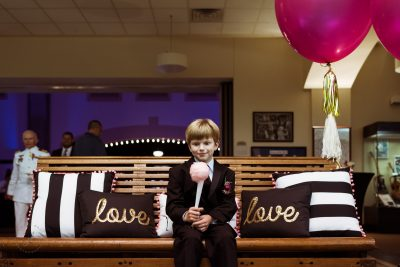 "The ring bearer contemplates his cotton candy at his uncle's wedding while sitting between two pillows that read ""love"" and ""love."""