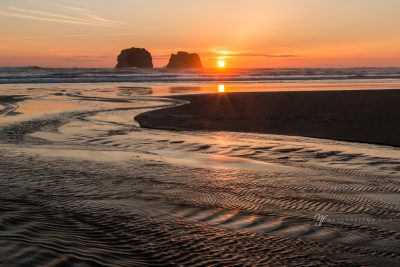 fiery sunset with rippled water at Rockaway Oregon feeling' the burn