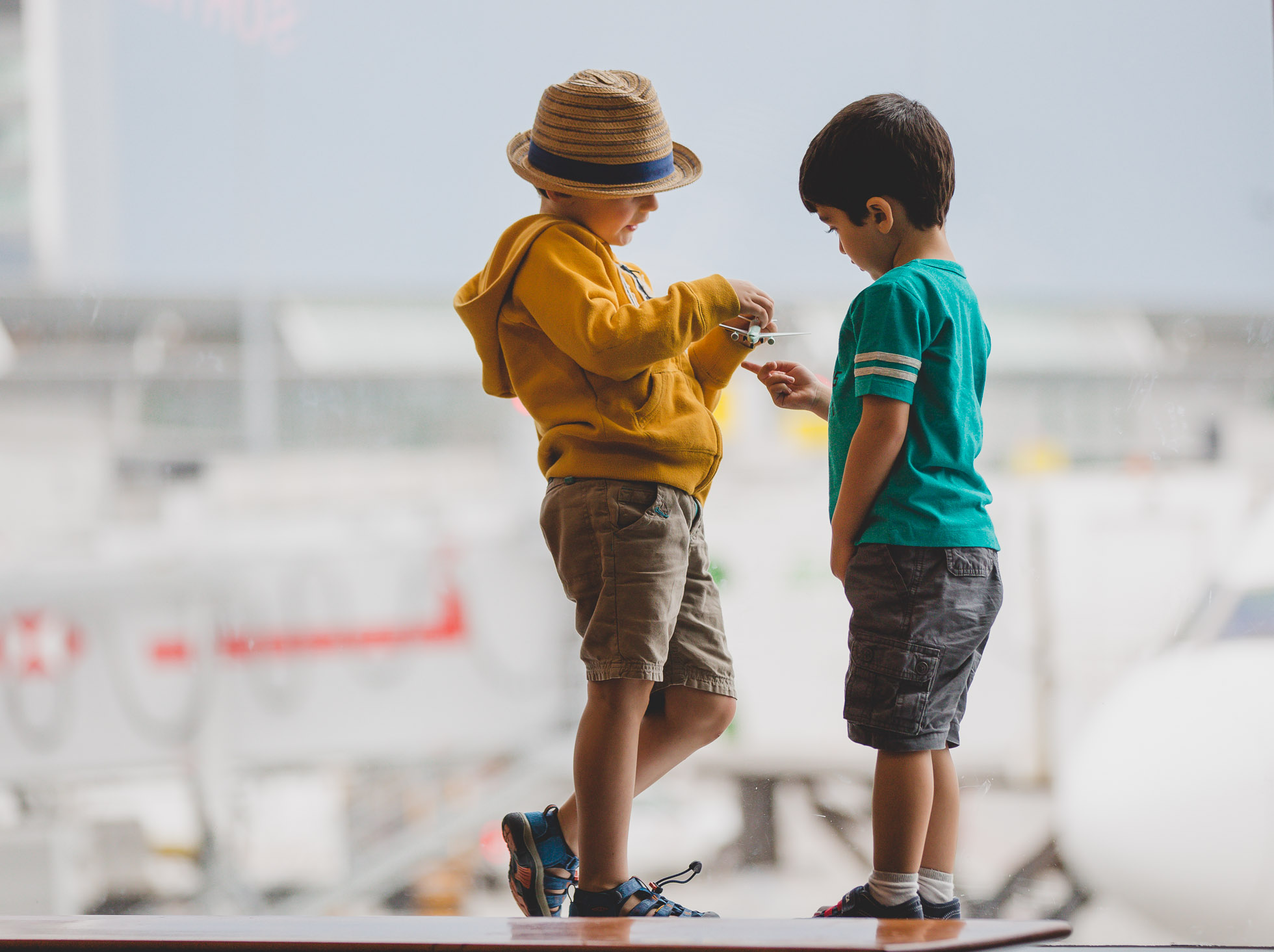 Two boys playing with a toy plane at the airport by Tami Keehn