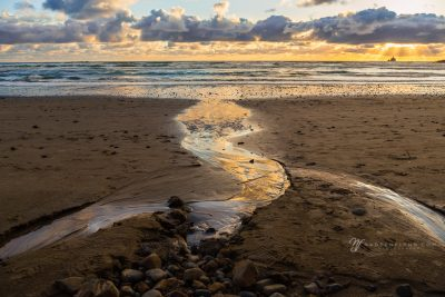 golden glow on water flowing from the beach into the ocean