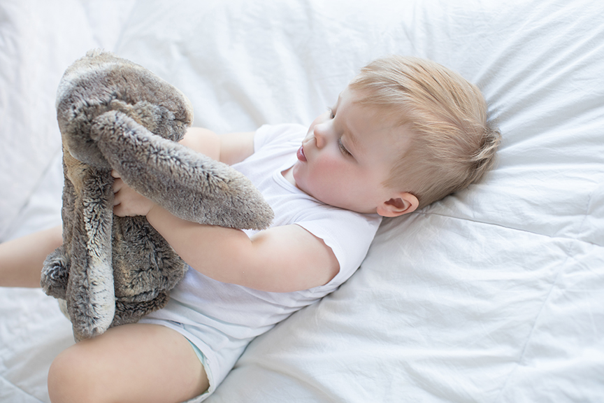 Little boy laying on bed playing with stuffed animal.