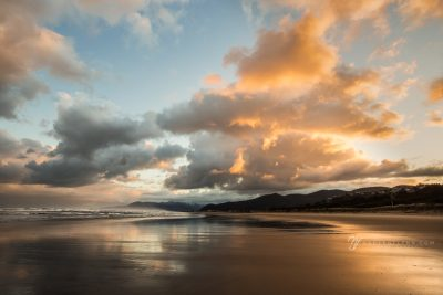 dramatic orange clouds at sunrise on Rockaway Beach, Oregon