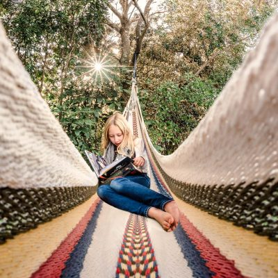 colorful-wide-angle-fisheye-everyday-photo-of-girl-reading-barefoot-in-hammock-on-sunny-day-in-backyard-in-New-Zealand-2