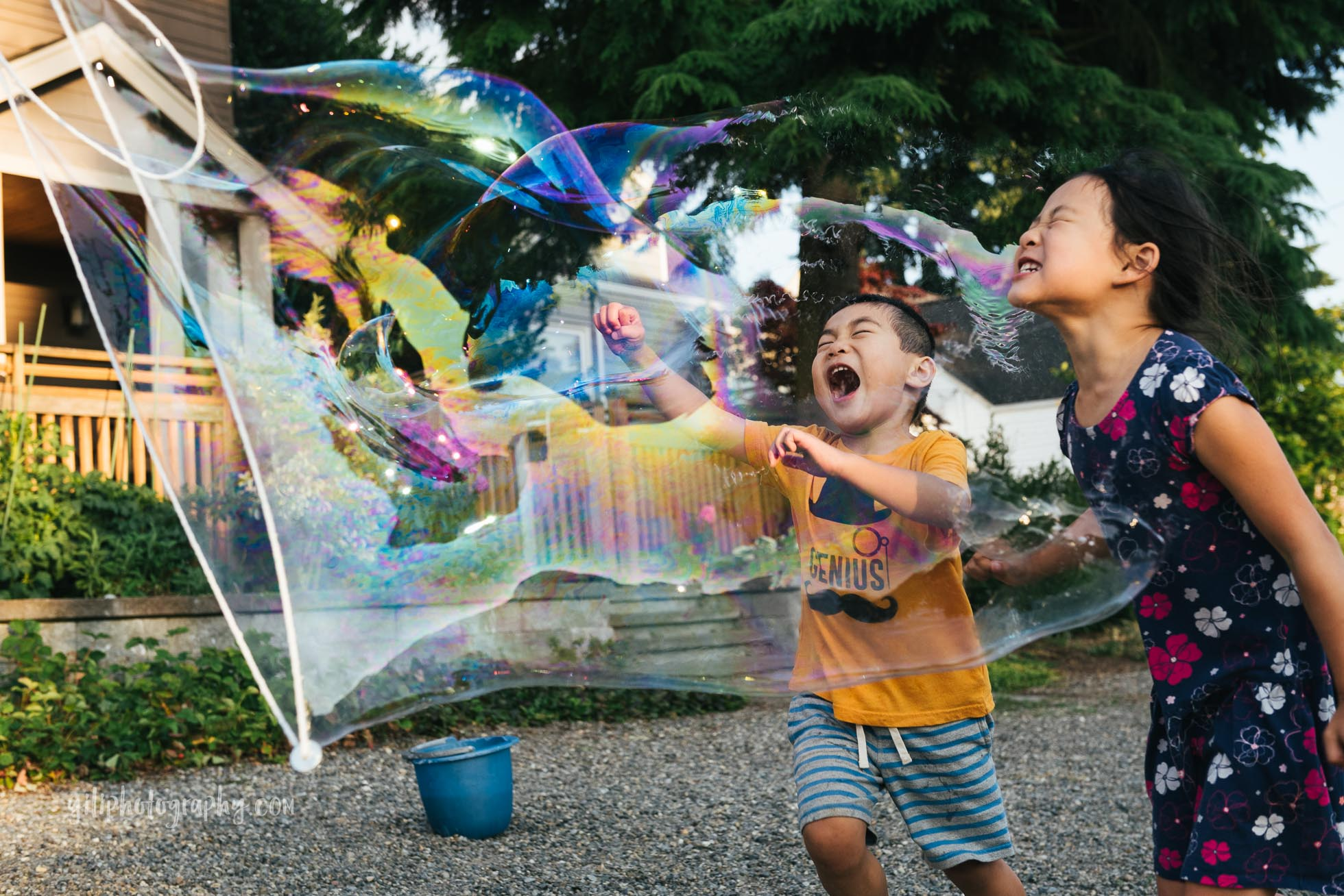 Giant bubble popping in the faces of two children laughing