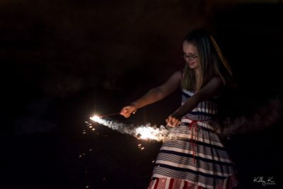 Joyful girl with sparklers, twirling in patriotic dress