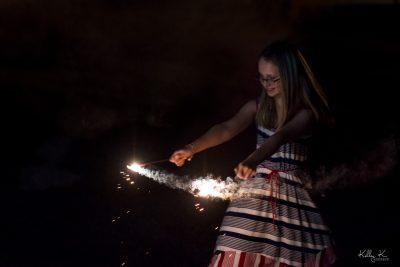 Joyful girl with sparklers, twirling in patriotic dress