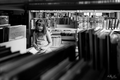 Tween girl sitting to read a book in the library, framed through bookshelves