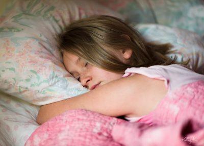 Tween girl sleeping in, under a pink quilt