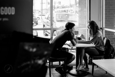 "A man looks into the eyes of the woman he loves, completely captivated by her. They are in Starbucks and in the foreground is the word, ""good."" A candid street capture with Nikon D750 and 35 f/1.4 lens."