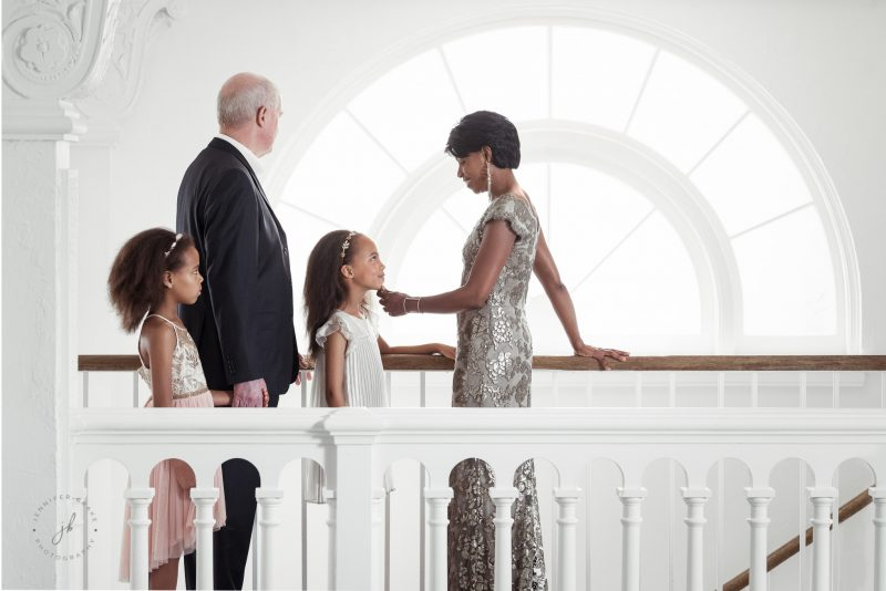 A mother raises her daughter's chin to make eye contact with her while dad and sister look on. Taken in an old renovated hotel on the mezzanine level, shot across a balcony with 50 mm f/1.4 Nikon lens, Nikon D750 camera.