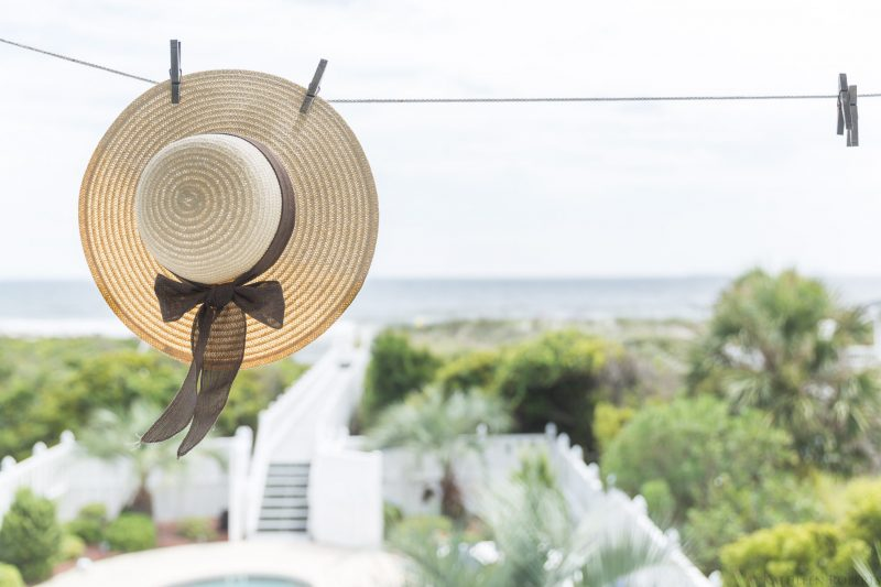 straw hat hanging from clothesline with view of the ocean