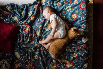 Baby laying next to cat on flowery blanket