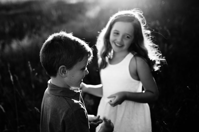 Black and white photo of siblings laughing and playing together