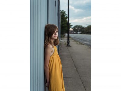 An adolescent girl wearing an orange dress stands and makes eye contact while leaning against a teal wall in the city, near downtown South Bend.