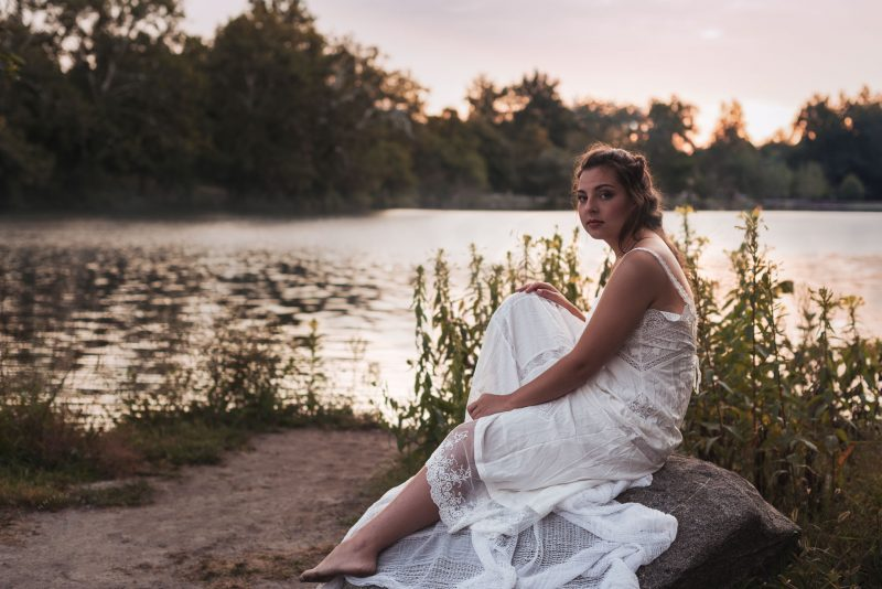 a high school senior girl relaxes on a rock in front of a foggy lake during golden hour, looking directly at the camera.