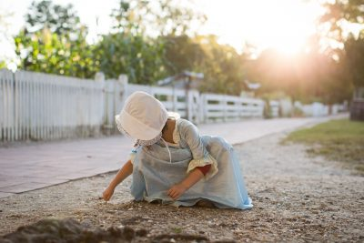 Young girl in colonial dress playing in the dirt