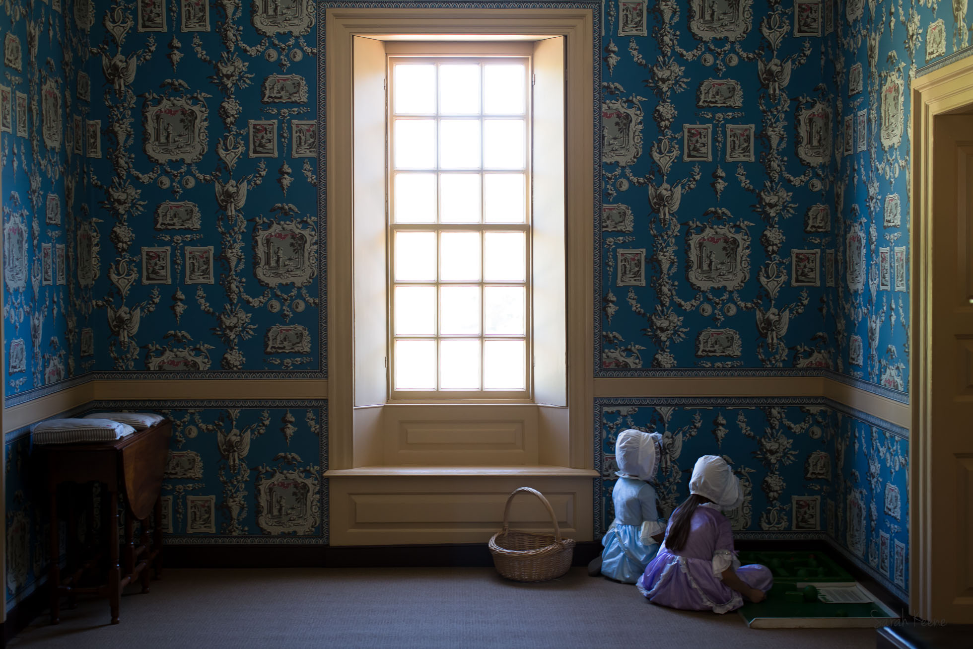Young girls in colonial dress playing in a historic home