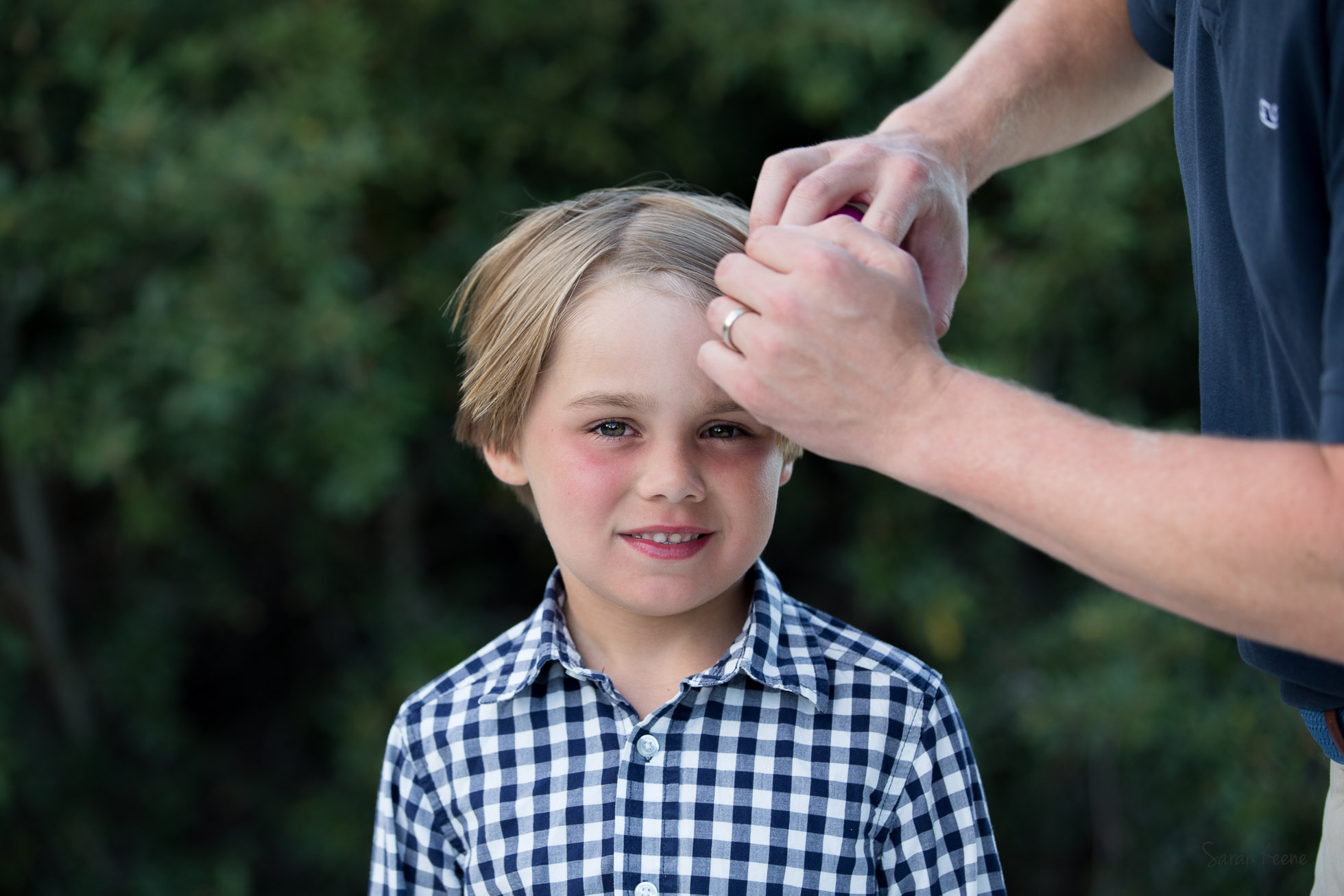 A father lovingly brushing hair before a portrait
