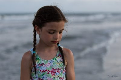 Blue hour photograph of a somber girl at the beach.
