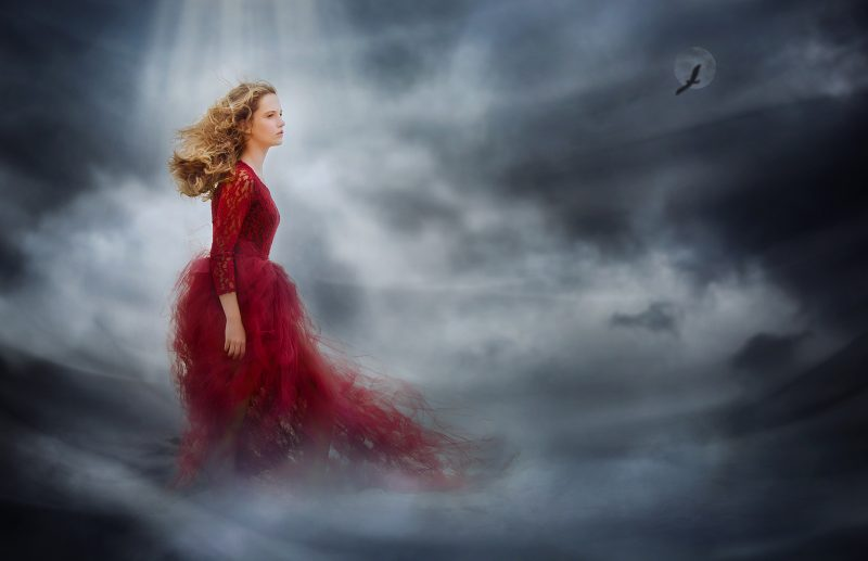 Canon fine art halloween image of a witch standing in a red dress in a dark cloud with smoke by Willie Kers