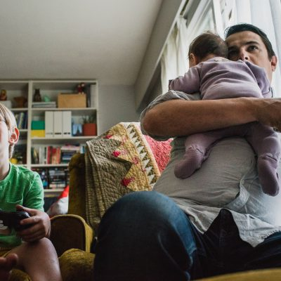 dad playing video games with his son while carrying his newborn on his shoulder
