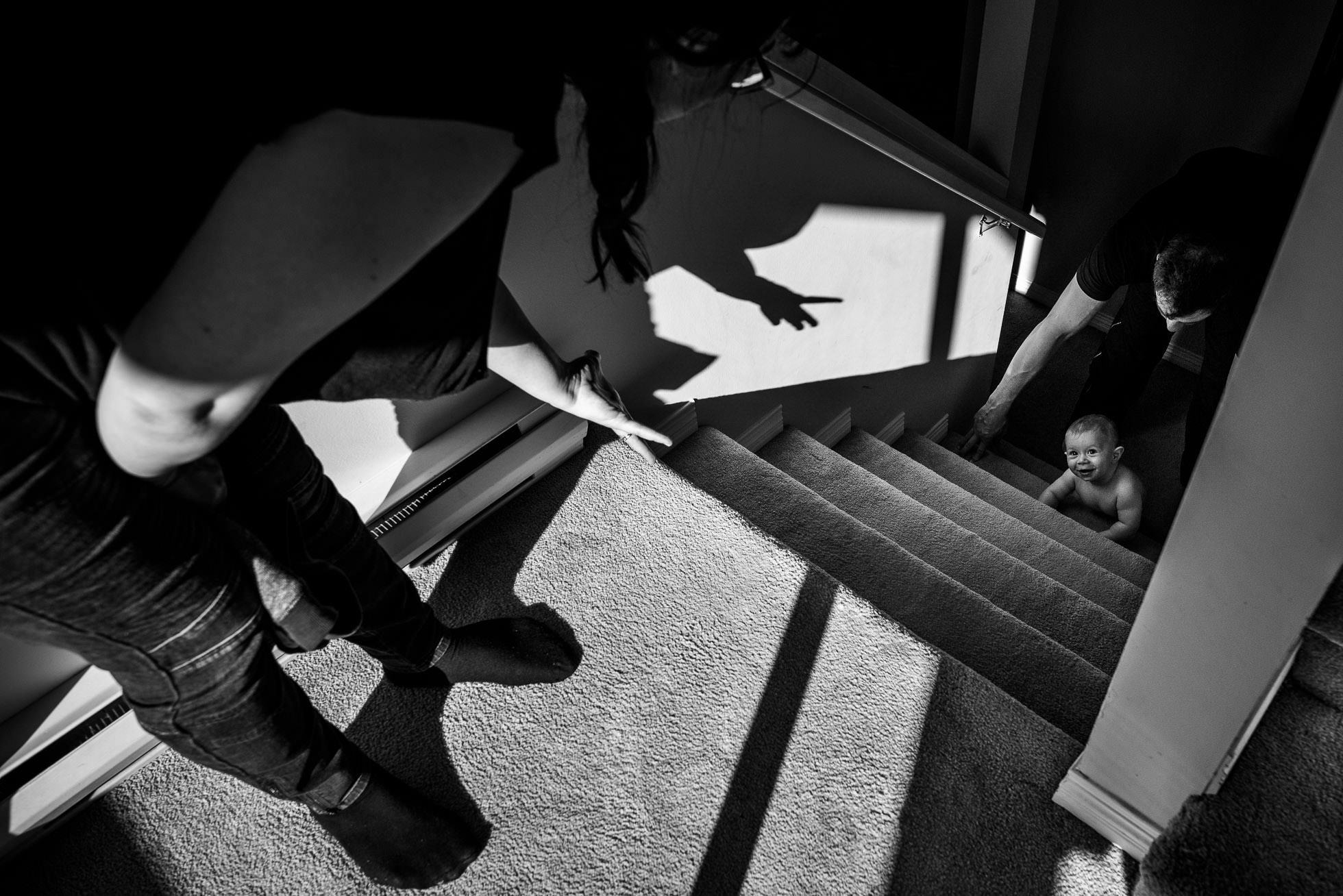 baby crawling up the stairs for the first time with mom and dad helping and encouraging
