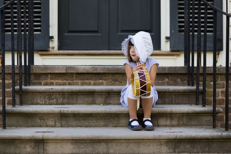 Young girl in colonial bonnet eating a cookie on porch steps by Sarah Keene