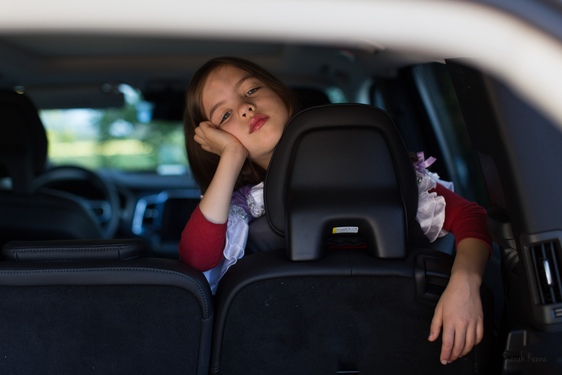 Bored little girl in the car by Sarah Keene