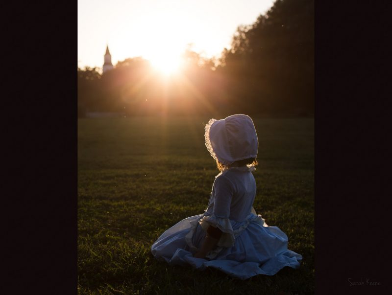 A young girl playing dress up in a bonnet with light by Sarah Keene