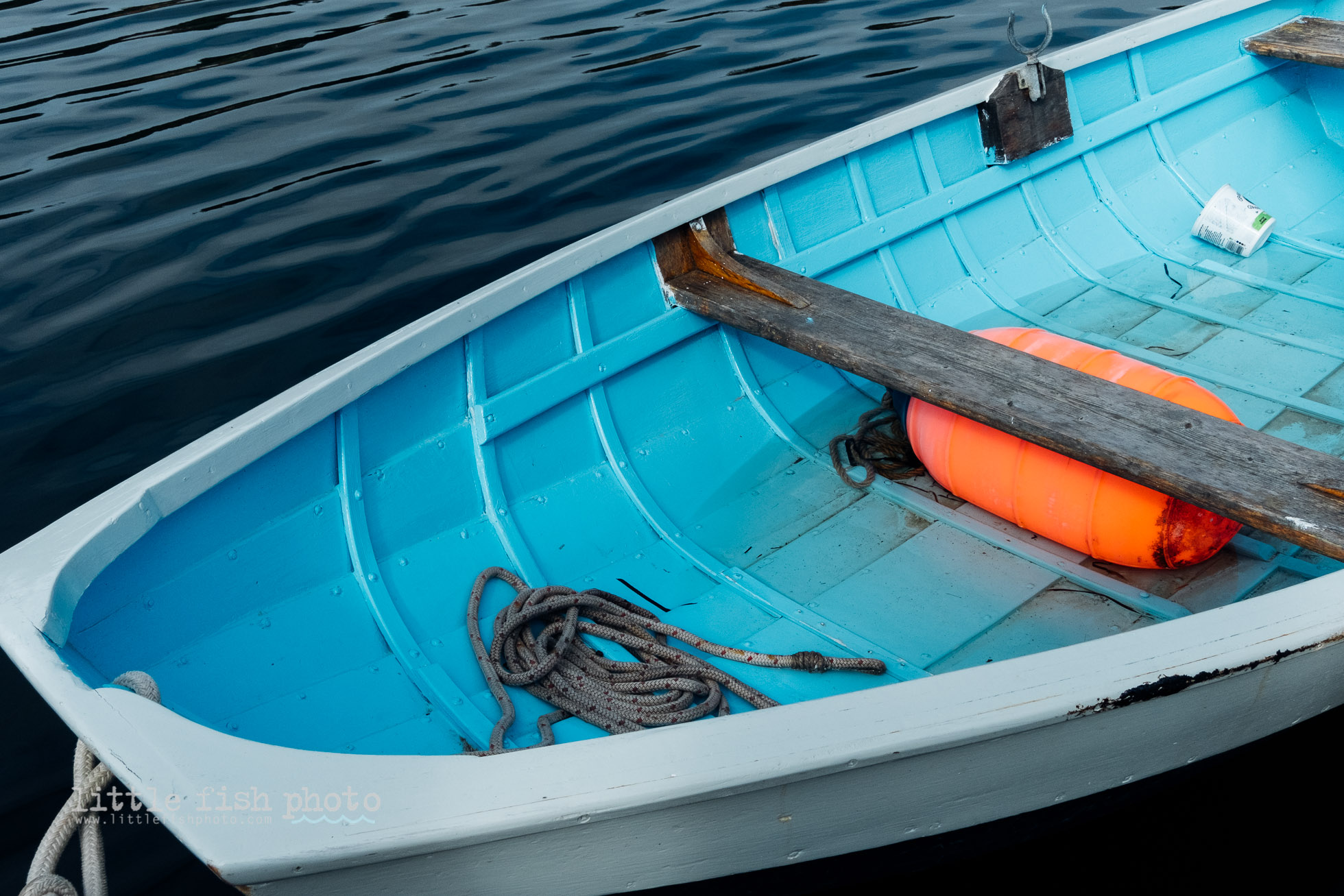 boat tied at pier with orange bouy