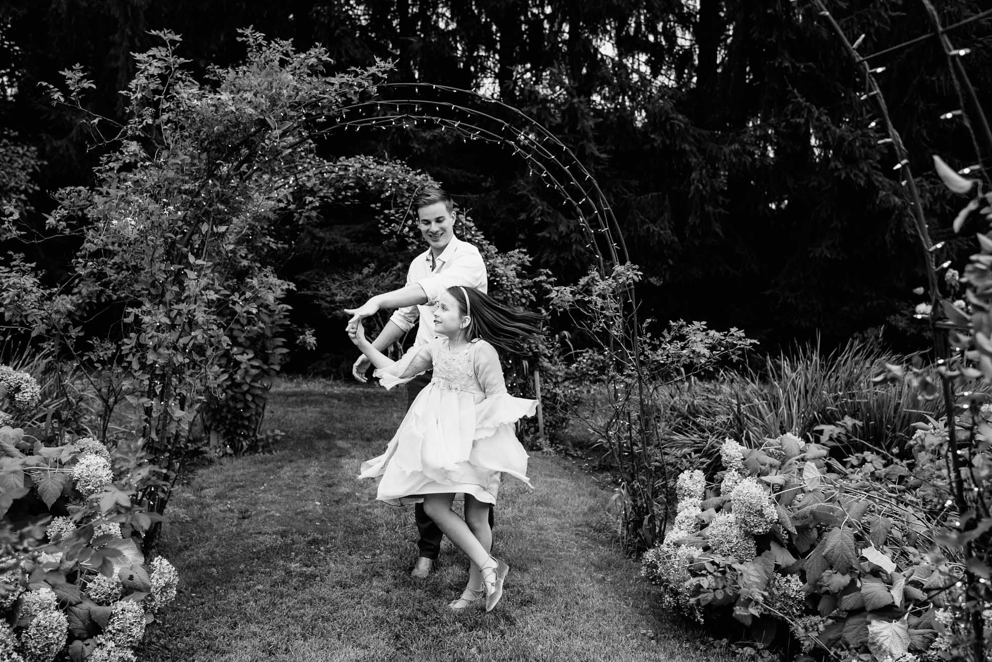 An older brother dances with his younger sister in a garden under arbors and arches, showing his soft side for his youngest sibling..