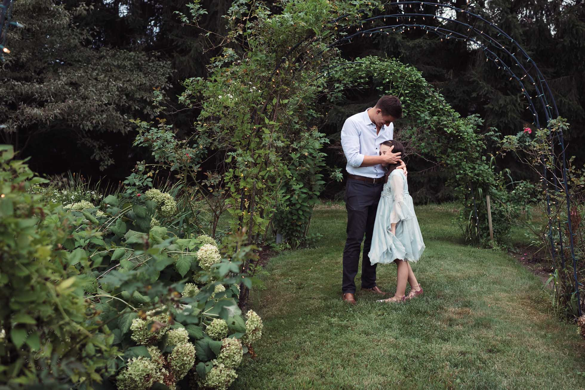 A big brother tenderly embraces his little sister, who adores him. They stand under arches of arbors and lights in a garden in late summer.