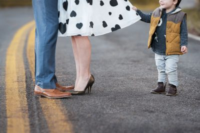 A little boy tries to get his mother's attention while her attention is directed to his father. He tugs at her heart-print skirt with an ornery smile.