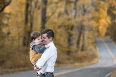 A father interacts with his smiling and curious toddler son while standing on a tree-lined road in South Bend, Indiana in the fall season.